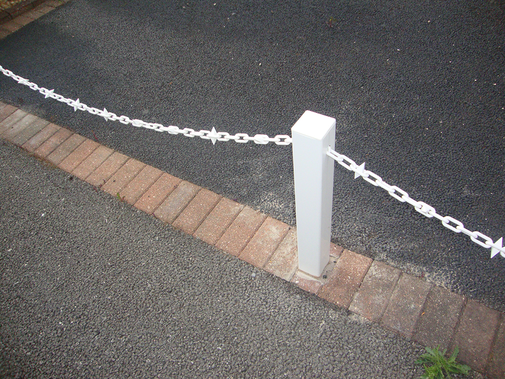 White Fence Post With White Chain and Diamond Driveway